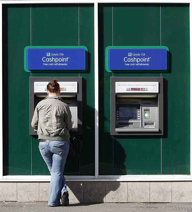 A woman uses a Lloyds TSB's ATM in Loughborough, central England.