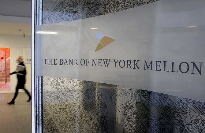 A woman walks past a logo at the office of the Bank of New York Mellon in Brussels, Belgium.
