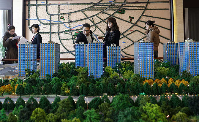 Visitors look around a miniature of apartment complex at a showroom in Beijing.
