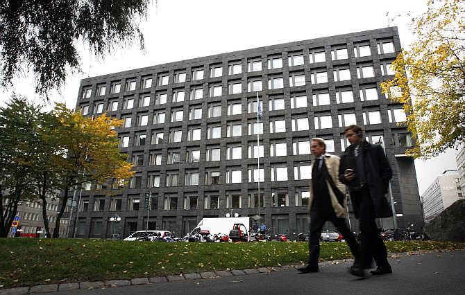 Pedestrians walk past the Swedish Riksbank headquarters in Stockholm, Sweden.