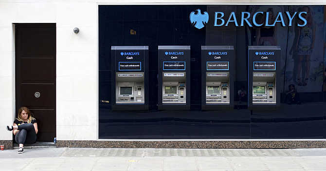 A woman sits close to a line of Barclays cash dispensers in central London.