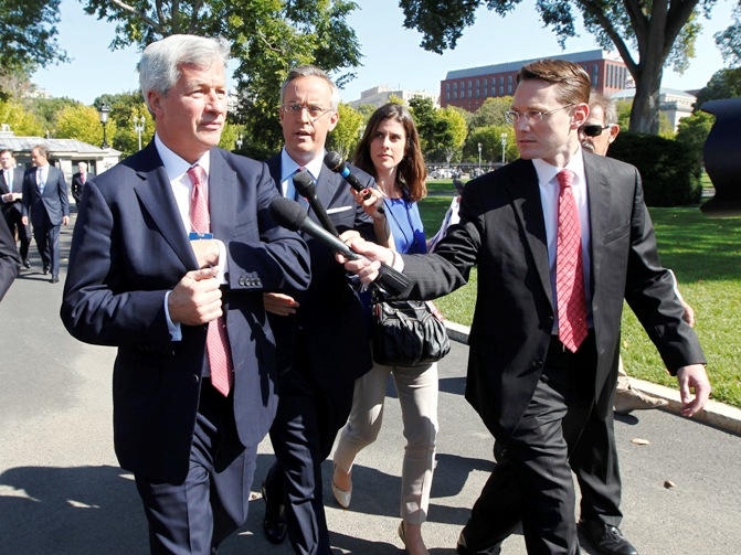 Jamie Dimon (L), chairman and CEO of JP Morgan Chase, is questioned by journalists as he and other CEOs arrive at the White House in Washington, October 2, 2013, for a meeting of the Financial Services Forum with US President Barack Obama.