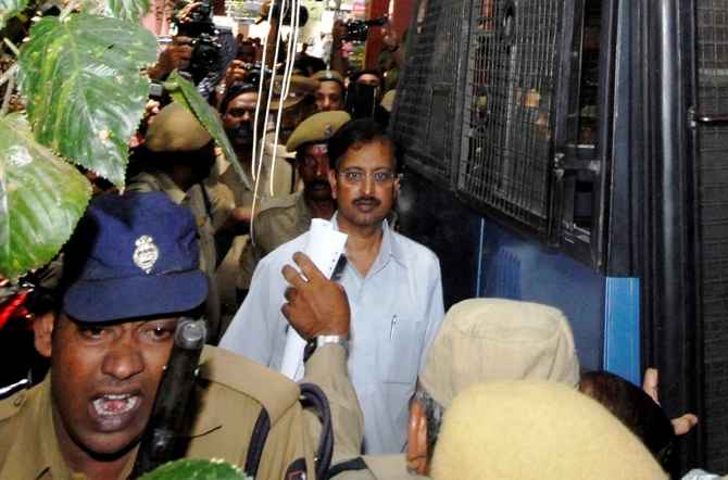 Ramalinga Raju (C), founder and former chairman of fraud-hit Satyam Computer Services, is escorted from a court in Hyderabad, April 9, 2009.