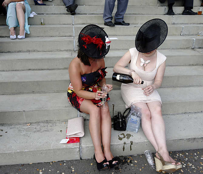 Racegoers drink champagne during the racing on Ladies Day during the Epsom Derby festival in Epsom, southern England.
