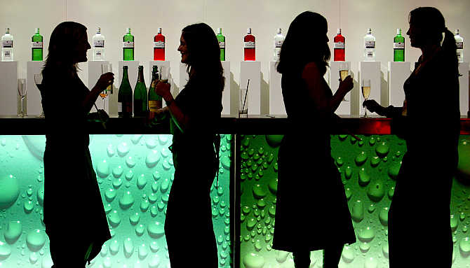 Women are silhouetted as they drink at a party in a bar in central London.