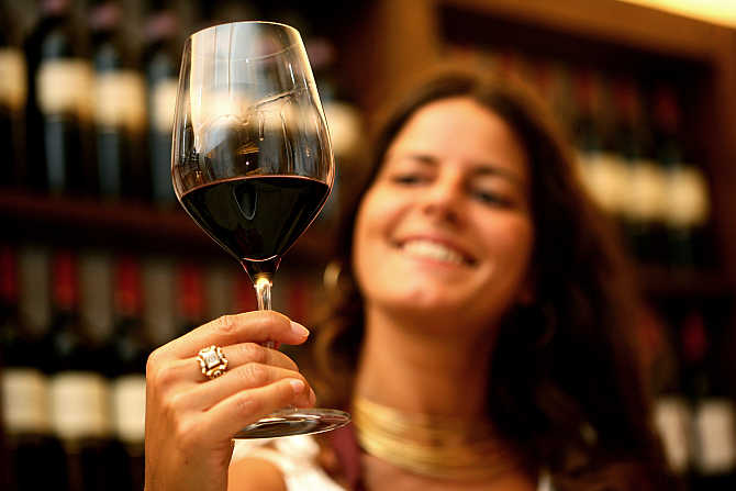 Federica Bon checks a glass of wine in the cellar of the Arnaldo Caprai vineyard, as the harvest of Sagrantino grapes begins near the Umbrian town of Montefalco, Italy.