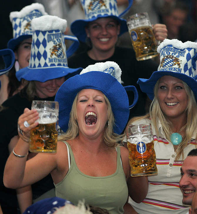 A woman shouts out as she drinks beer during the Munich's Oktoberfest, Germany.