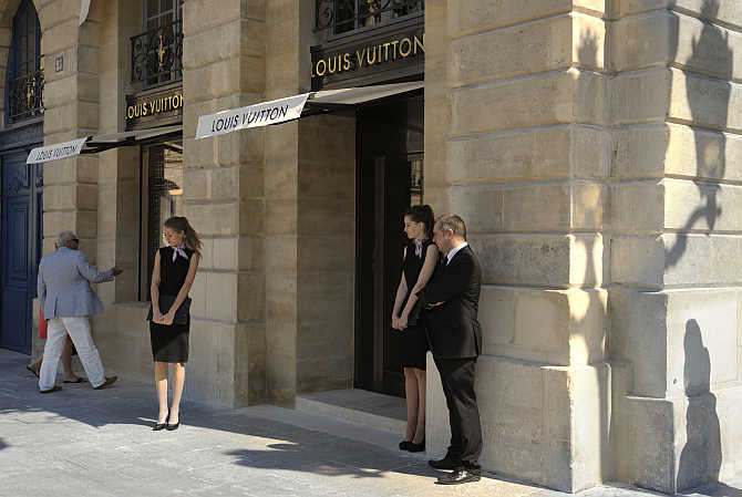 Hostesses stand in front of the entrance of LVMH's Louis Vuitton's jewellery store in Paris, France.