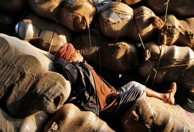 A labourer sleeps on sacks filled with aluminium utensils loaded on a hand cart along a road at a wholesale market in Kolkata.