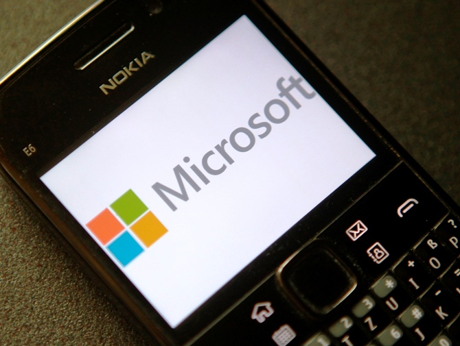 A photo illustration shows the Microsoft logo displayed on a Nokia phone.