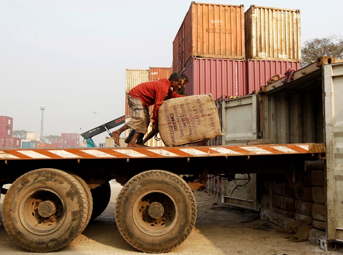 Labourers unload goods from a trailer at a port in Kolkata January 10, 2014.