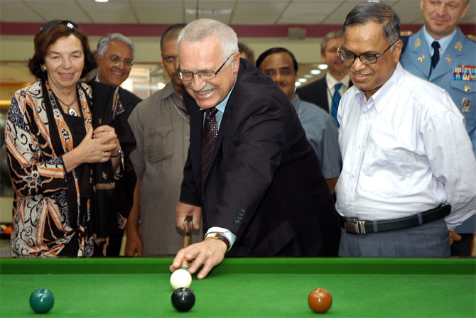 File photo of Vaclav Klaus (C), President of the Czech Republic, plays billiards as his wife Livia Klausova (L) and Narayana Murthy (R, white shirt), look on.