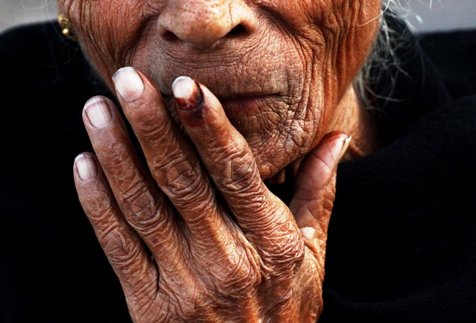 An elderly woman places her ink-marked finger on her lips after casting her vote outside a polling booth during the state assembly election in Delhi December 4, 2013.