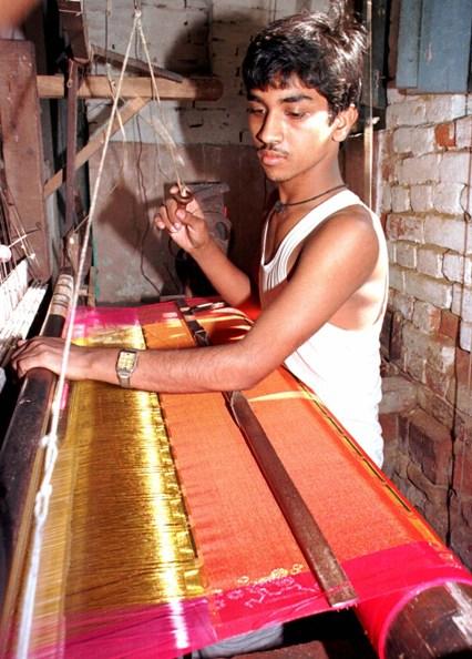 A weaver works on a silk sar