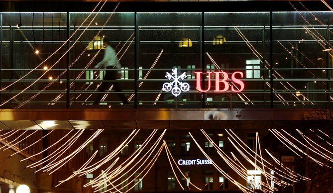 A man walks past the logo of Swiss Bank UBS on a footbridge connecting two office buildings in Zurich.