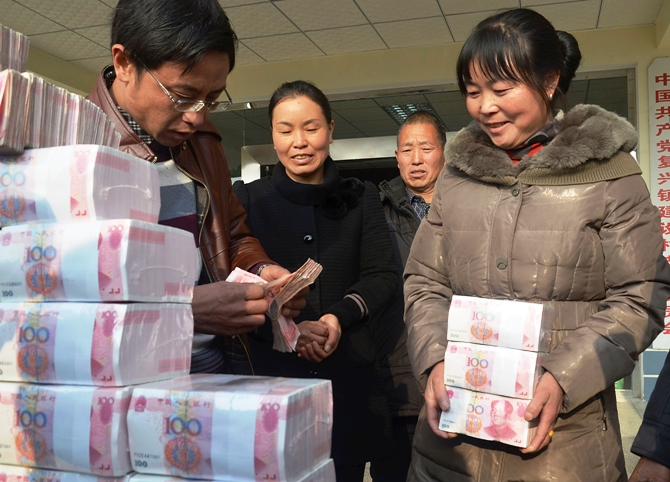 Ling Xuxia collects her 314,000 yuan ($51,935) year-end bonus at Jianshe village, Liangshan, Sichuan province, January 14, 2014.