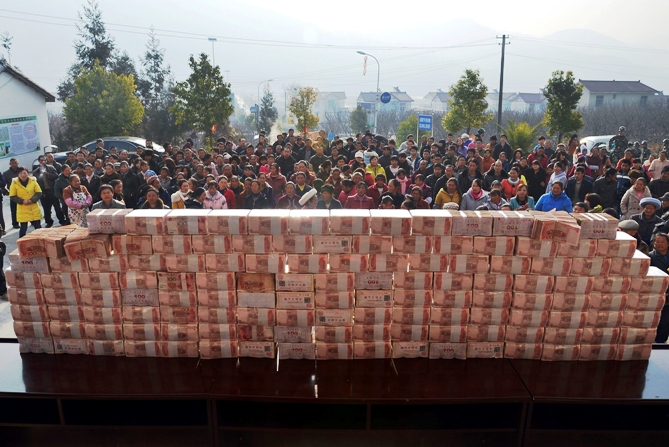 Villagers wait to collect their year-end bonus at Jianshe village, Liangshan, Sichuan province, January 14, 2014.