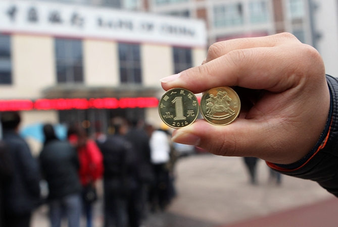 A resident displays newly-issued one Chinese yuan souvenir coins, to commemorate the Year of the Horse, as people queue to exchange the coins outside a Bank of China branch in Neijiang, Sichuan province December 24, 2013.