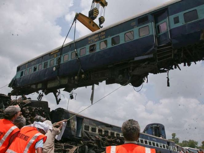 Rescue workers help to move a carriage, lifted by crane, from a passenger train which derailed near Fatehpur.