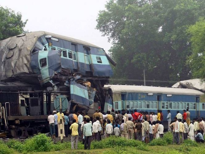 Onlookers stand beside the damaged carriages of a train at the site of an accident near Badarwas station.