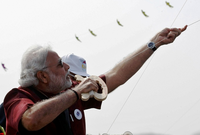 Narendra Modi, prime ministerial candidate for India's main opposition BharatiNarendra Modi flies a kite at the international kite festival in Ahmedabad January 12, 2014.