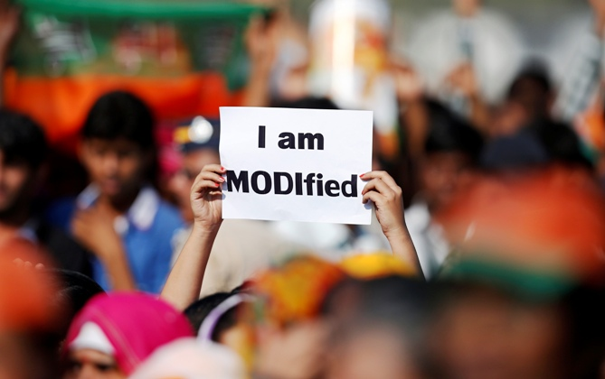 A supporter of Narendra Modi holds a placard during a rally being addressed by him in Mumbai December 22, 2013.
