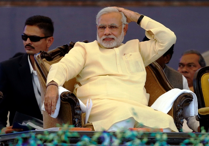 Gujarat's chief minister Narendra Modi sits before addressing his party's supporters during a rally ahead of the 2014 general elections, in Mumbai December 22, 2013.