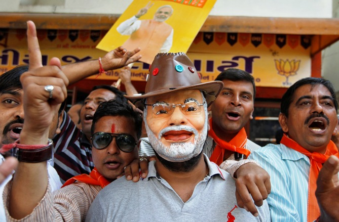 A supporter wearing a mask of Gujarat's Chief Minister Narendra Modi celebrates outside the party's headquarters in Ahmedabad December 8, 2013.