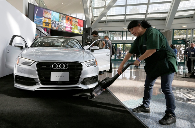 A woman vacuums in front of the new Audi A3 sedan before the start of the 2013 Los Angeles Auto Show in Los Angeles, California, November 19, 2013.