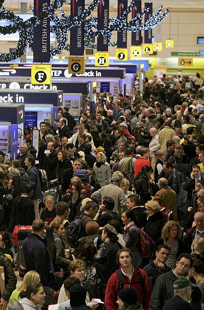 Passengers queue to check-in at terminal 1 of Heathrow Airport.