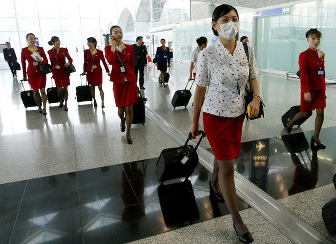 A masked Cathay Pacific Airways flight attendant walks with her crew at Hong Kong international airport.