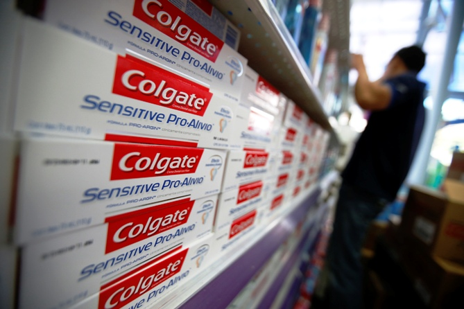 A worker arranges Colgate products on a shelf at a supermarket.
