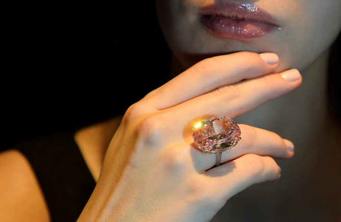 Model Annabeth Murphy-Thomas poses with The Pink Star diamond at Sotheby's auction house in central London October 24, 2013.