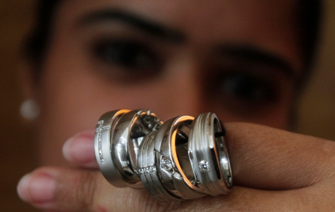 A saleswoman displays platinum rings for the camera at a jewellery showroom in New Delhi.
