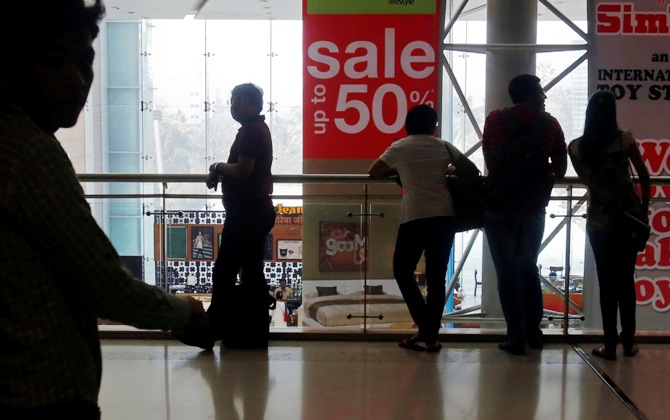 Shoppers are silhouetted as they stand near a sign advertising a sale at a shopping mall in Mumbai.
