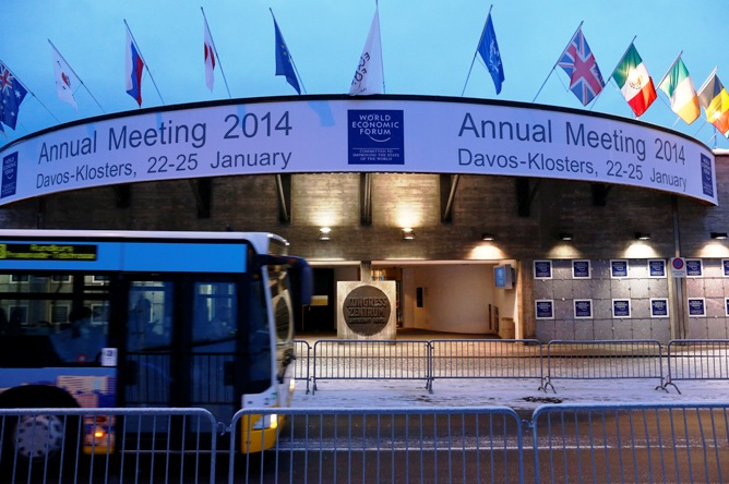A bus drives past the entrance of the congress centre for the annual meeting of the World Economic Forum (WEF) 2014 in the early morning in Davos January 21, 2014.