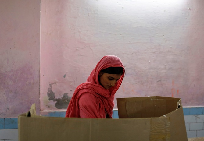 A woman casts her vote inside a polling booth during the state assembly election in the old quarters of Delhi December 4, 2013.
