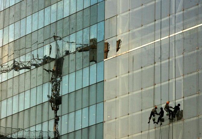 Workers clean windows on a building under construction in Hyderabad.