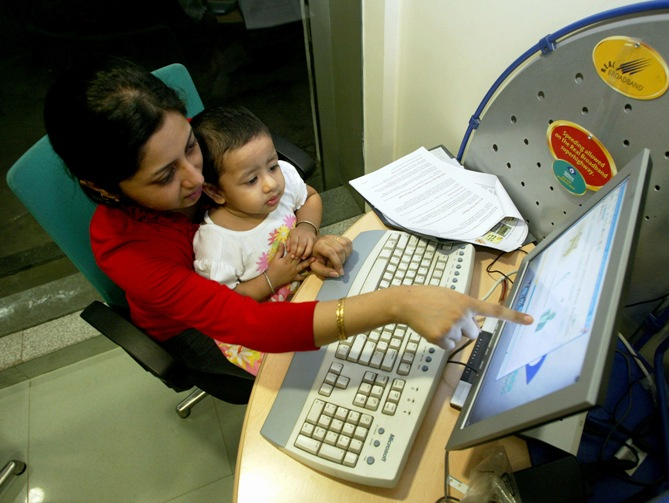 This file photograph shows Sangeeta Dutta and daughter Anushna sit at a high-speed broadband Internet cafe in Kolkata.