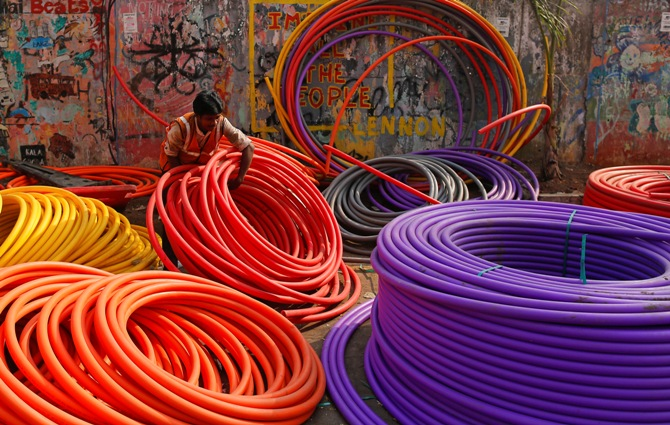 A labourer works amid rolls of underground telephone cable pipes on the side of a road in Mumbai.