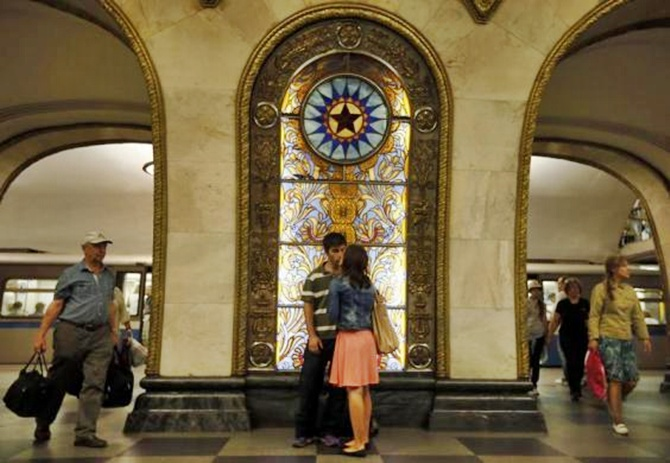 A couple in front of a stained glass panel in Novoslobodskaya metro station, which was built in 1952, in Moscow.