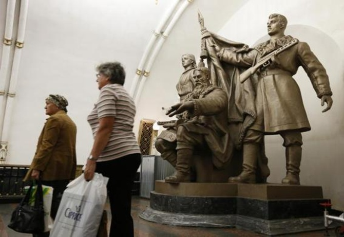 Women walk past a statue in Belorusskaya metro station in Moscow.