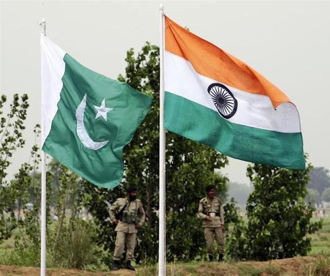 This file photograph shows Pakistani rangers standing near the Indian (R) and Pakistani national fla