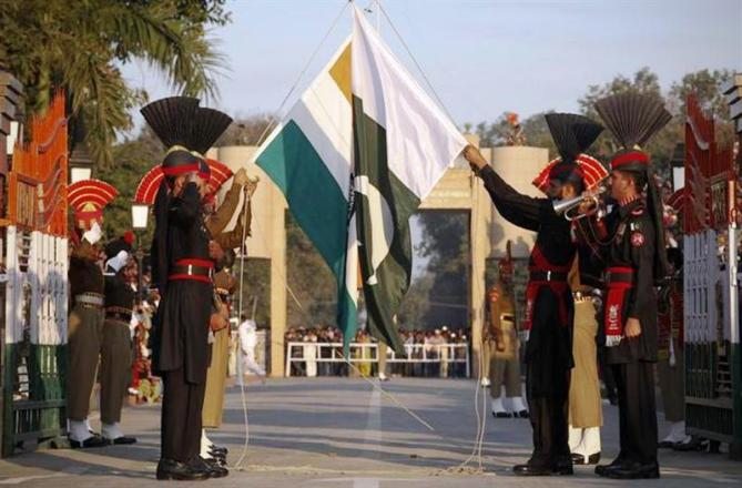 This file photograph shows Pakistan Rangers (R) and Border Security Force personnel taking part in the daily flag lowering ceremony at their joint border post of Wagah near Lahore.