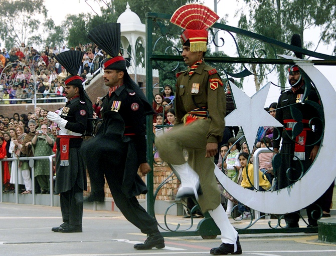 An Indian border security soldier (R) and Pakistani rangers (L) perform during a parade during a retreat ceremony at the Indo-Pak Joint check post in Wagha.