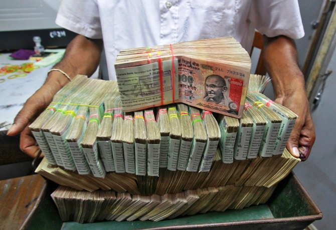 An employee poses with the bundles of Indian rupee notes inside a bank in Agartala.