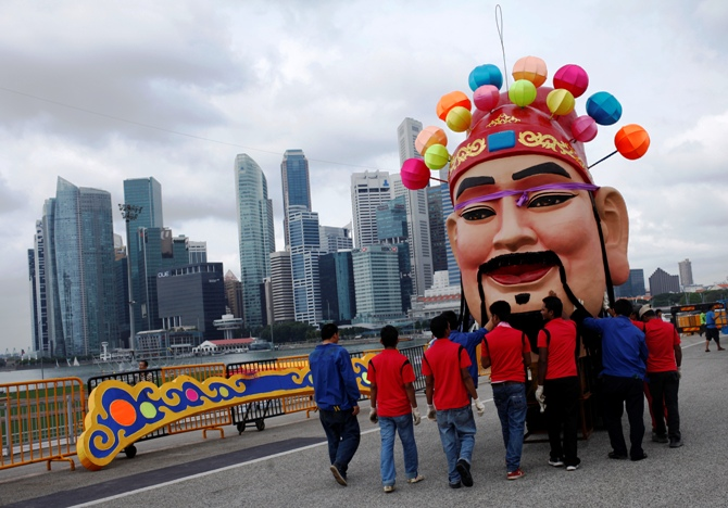 Workers assemble a God of Fortune statue as part of Chinese New Year decorations along the skyline of Singapore.