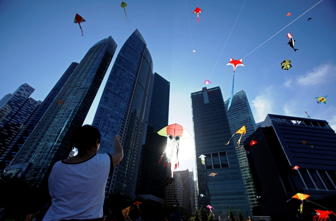 People fly kites during the annual Singapore Kite Festival at the central business district area of Marina Bay in Singapore.