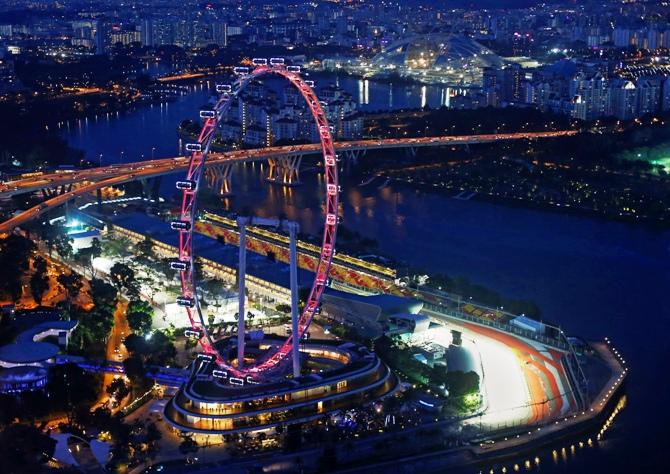 An aerial view shows the main grand stand and the Formula One pit building behind the Singapore Flyer observation wheel at dusk.