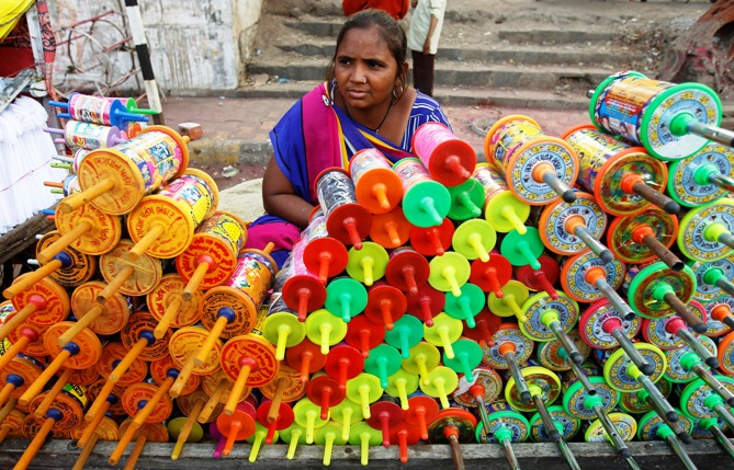 A vendor sits at her stall selling reels of thread used to fly kites, at a roadside kite market.